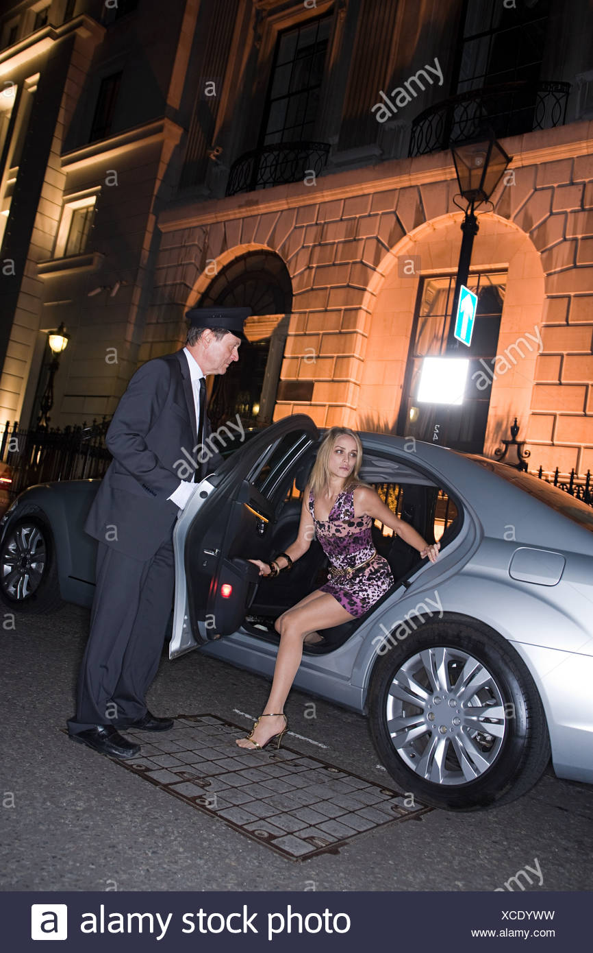 Wealthy woman getting out of car - Stock Image