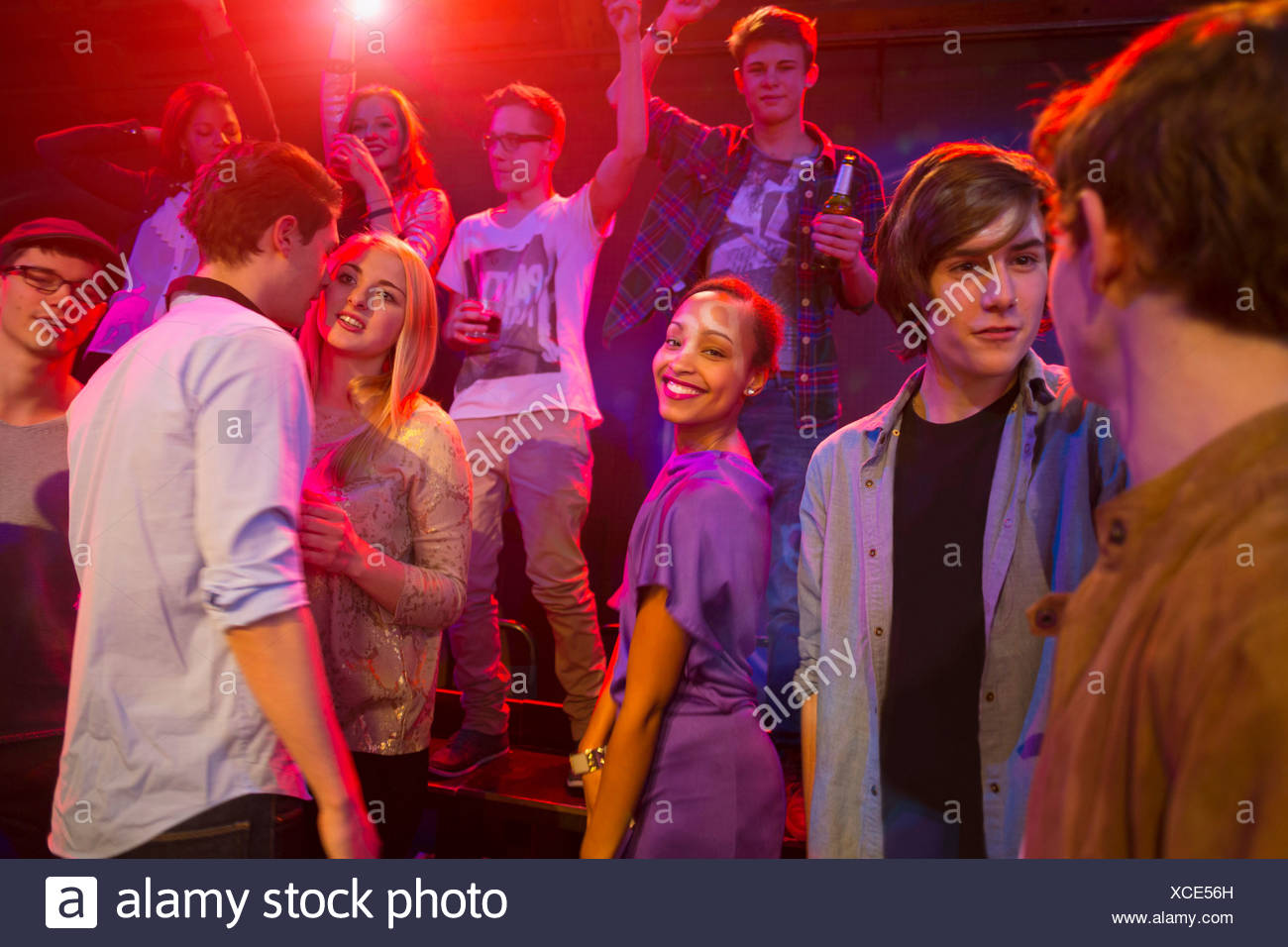 Group of people at party, dancing and smiling - Stock Image