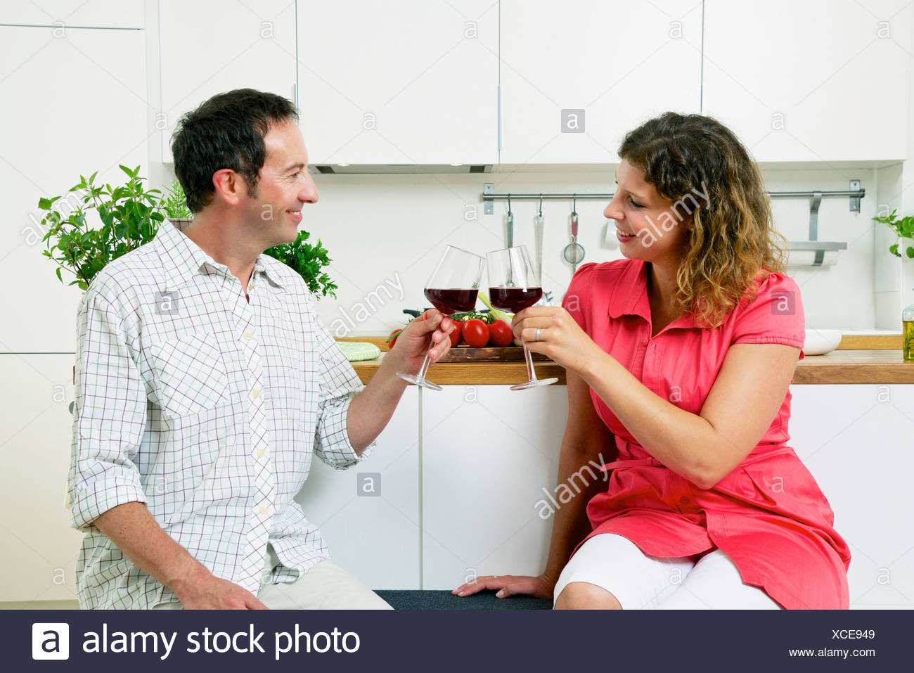 Couple In Kitchen Having Drinks - Stock Image