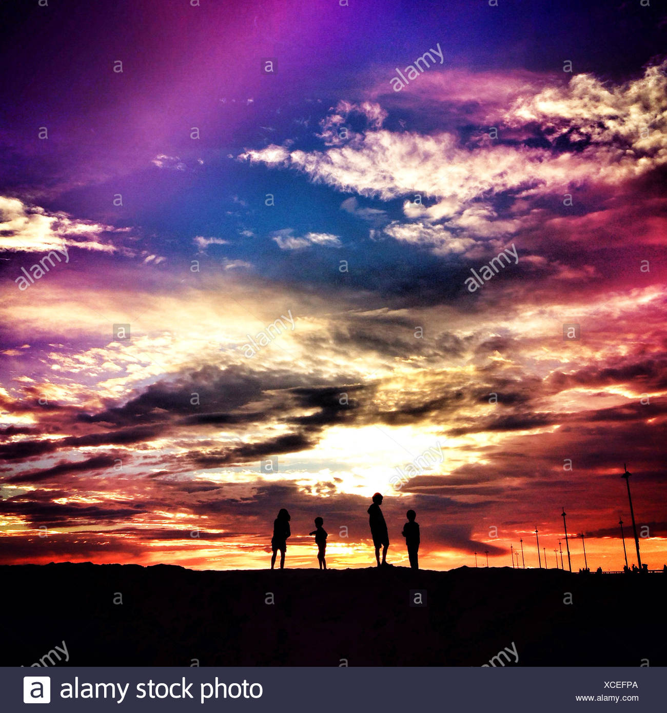 Silhouette of four children at sunset - Stock Image