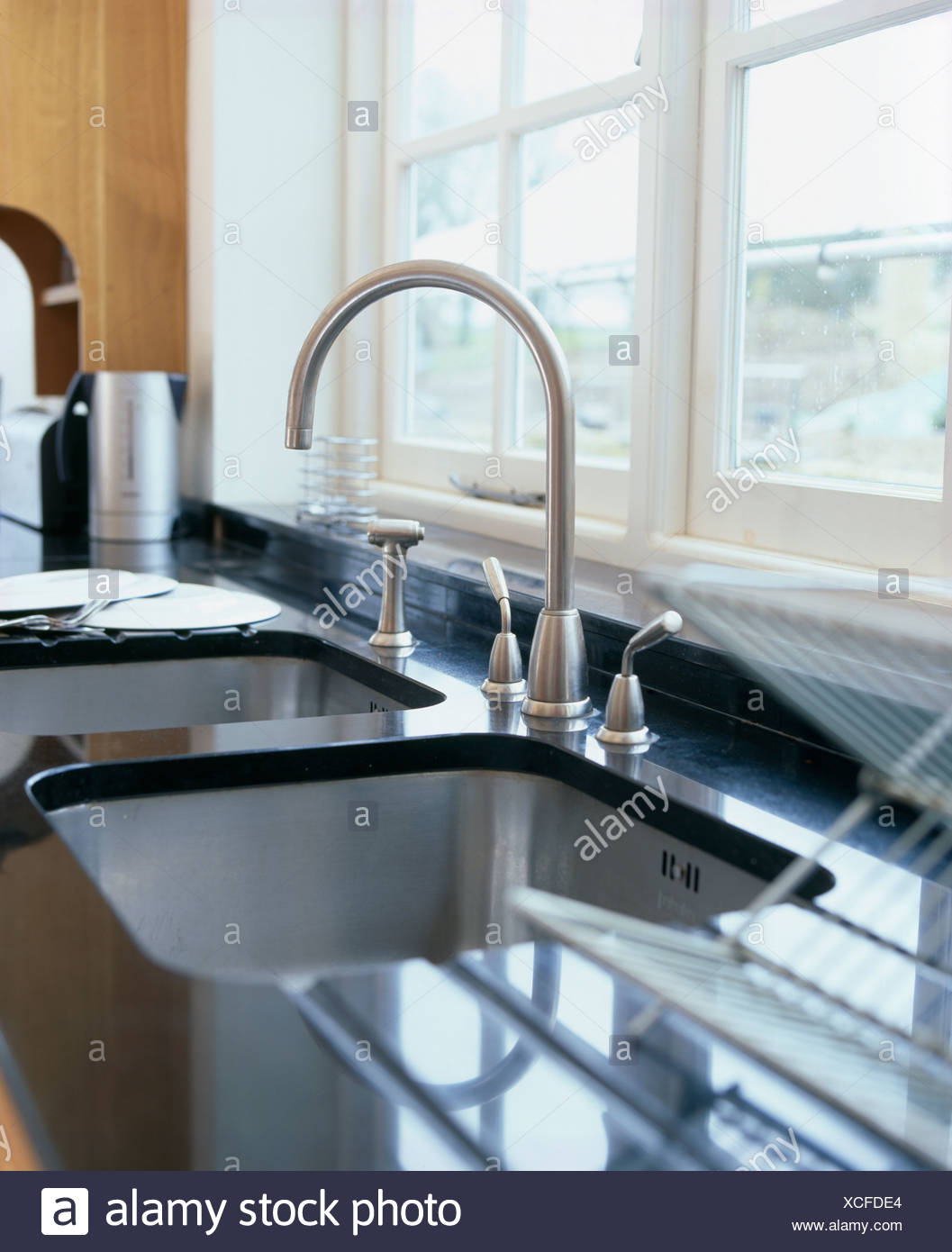 Close-up of stainless steel tap and under-set sink in black granite ...