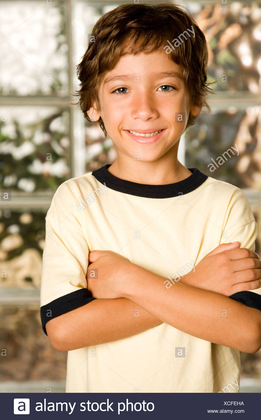little boy smiling arms folded - Stock Image