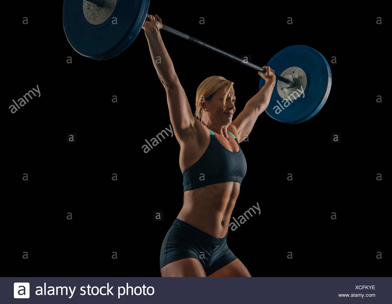 Young female weightlifter practicing barbell weightlifting snatch - Stock Image