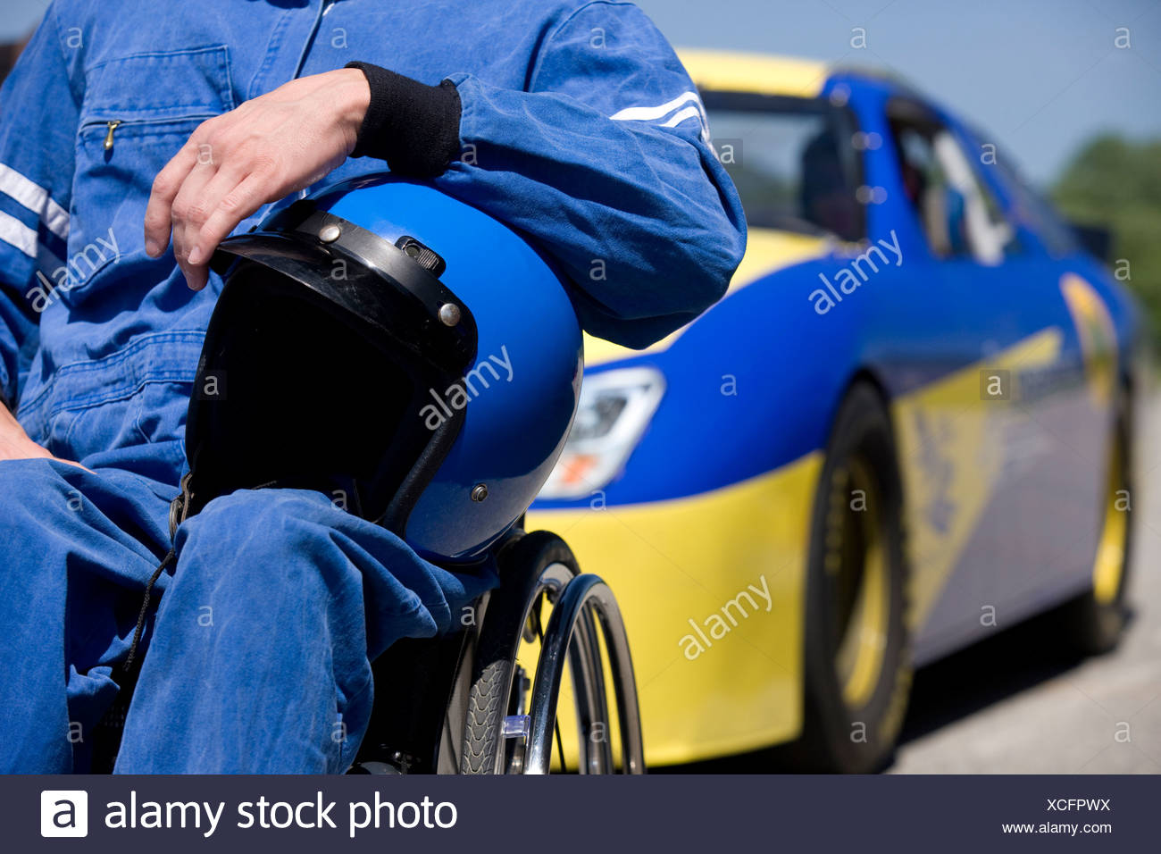 Disability race car driver, mid section, car in background - Stock Image