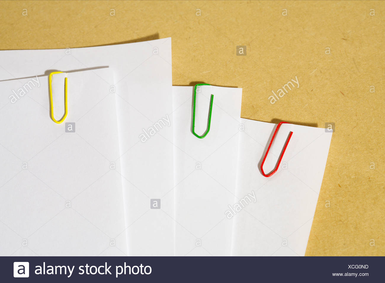Colored paper clips on white piece of papers - Stock Image