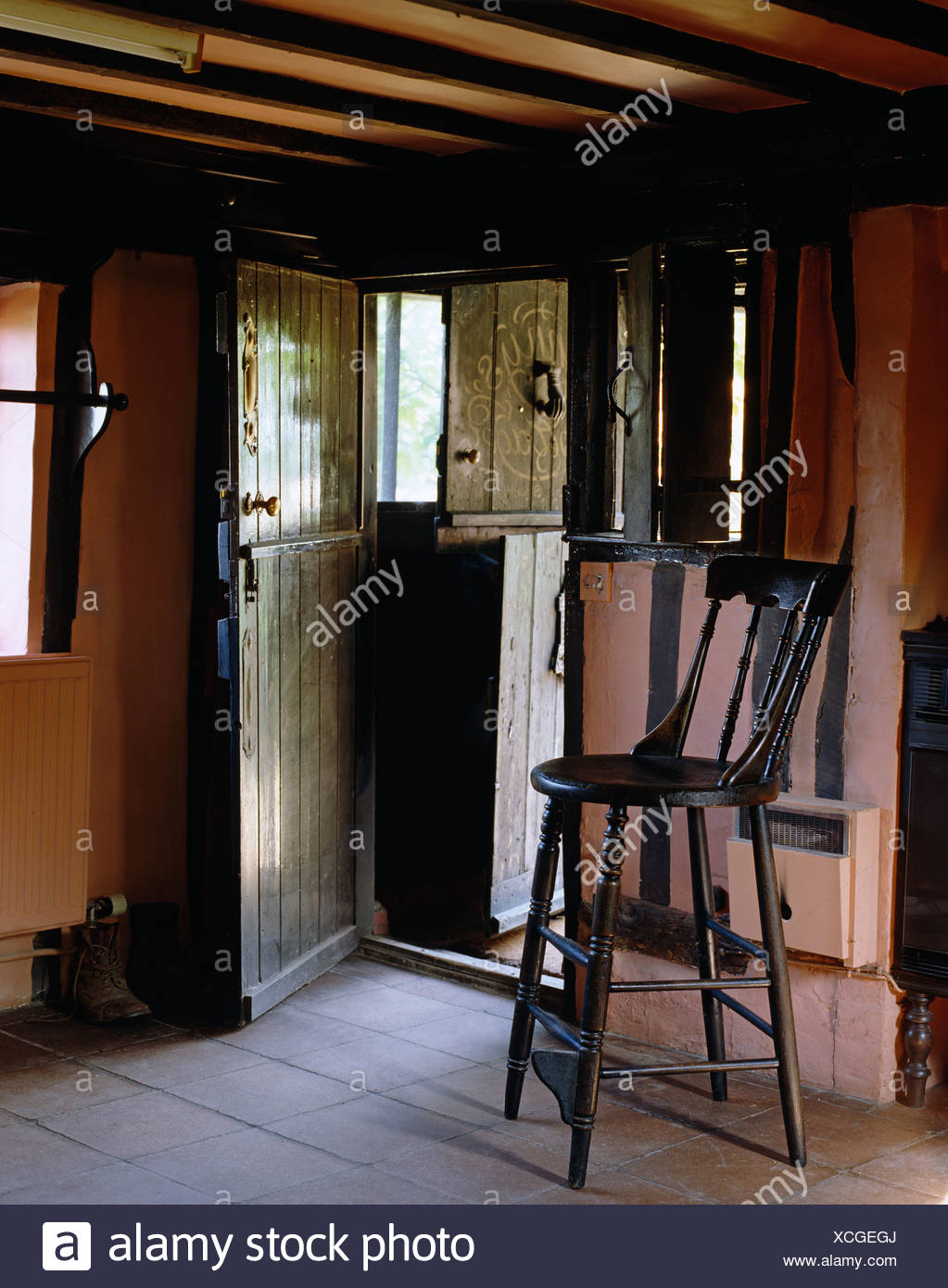 Antique High Chair In Tudor Cottage Hall With Stable Door And Tiled