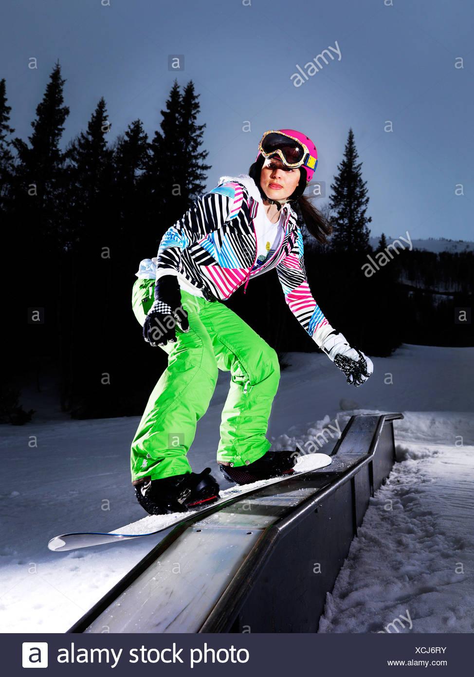 Girl board sliding on flat rail. - Stock Image