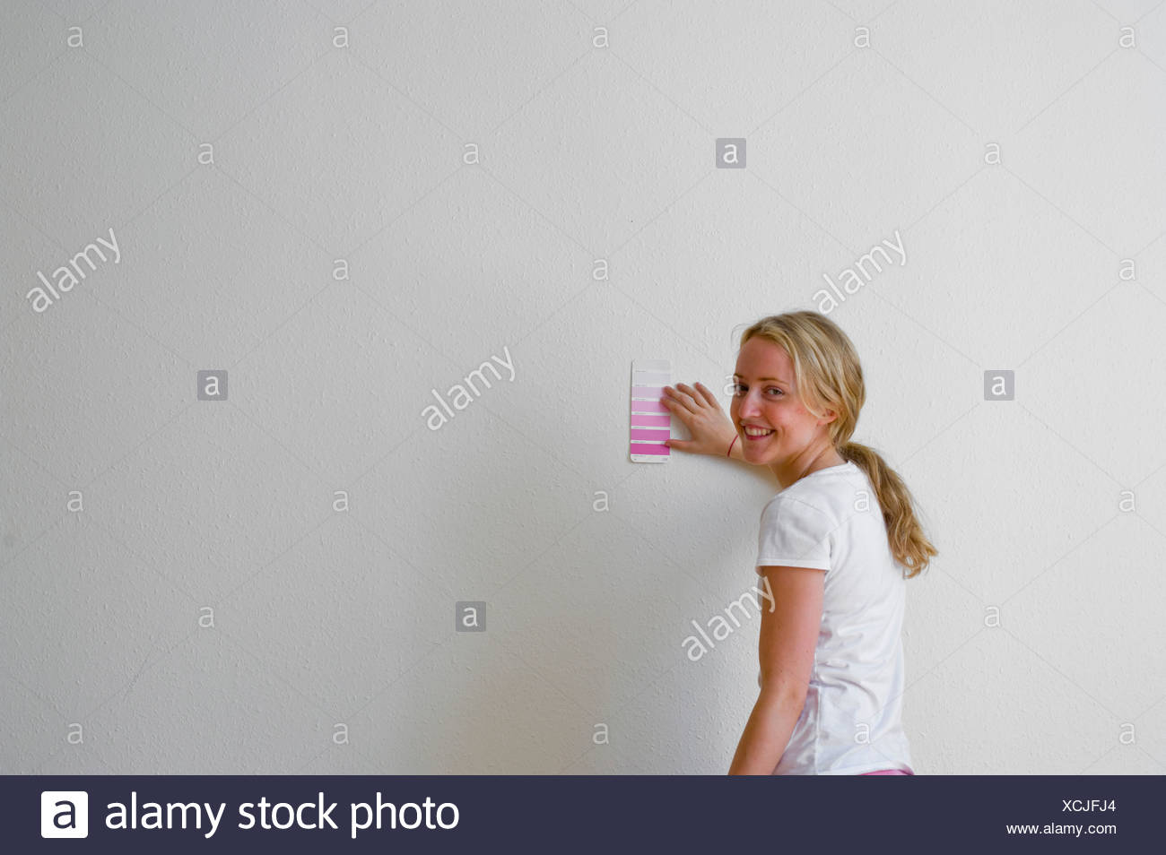 Woman standing against wall choosing colour - Stock Image