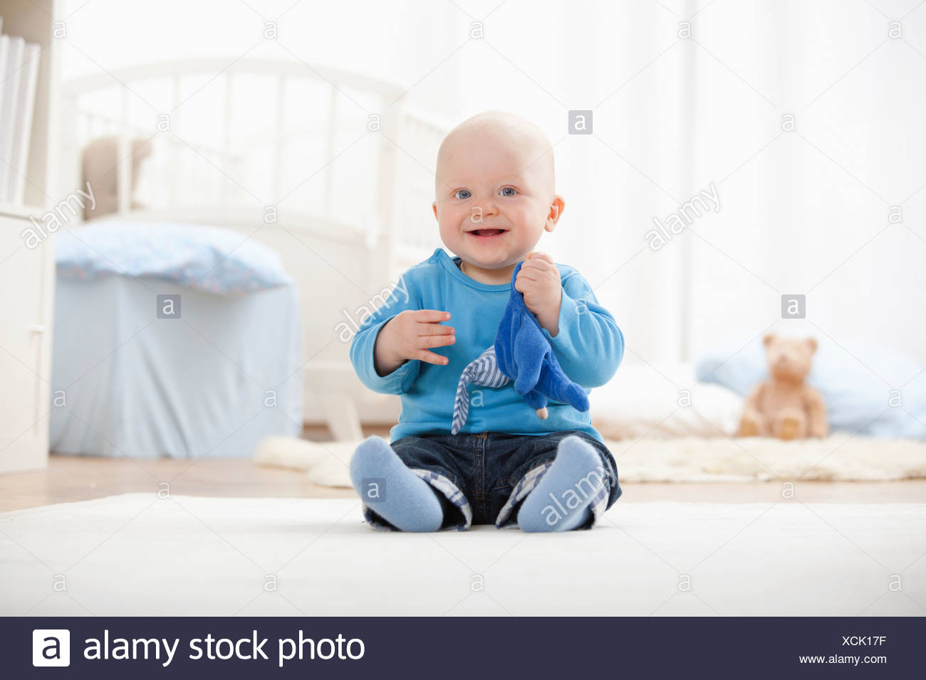 Baby boy playing with soft toy - Stock Image