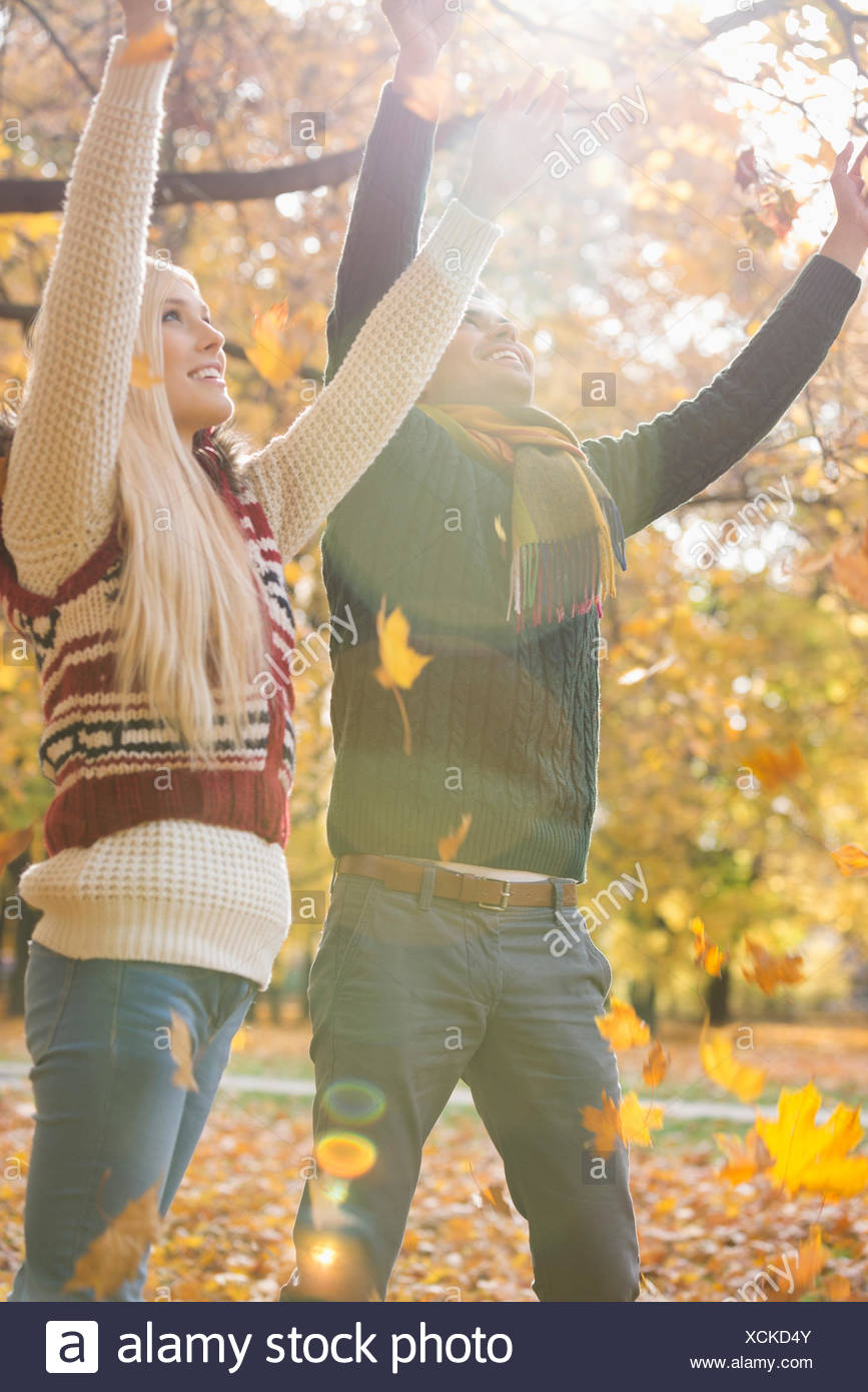 Happy young couple with arms raised enjoying falling autumn leaves in park - Stock Image
