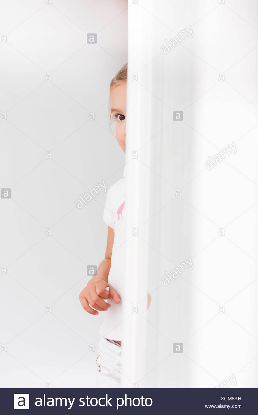 young girl looking around corner - Stock Image