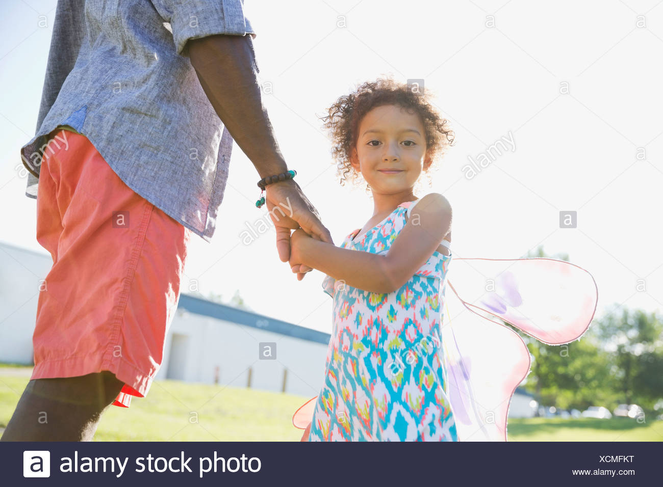 Portrait of cute girl holding fathers hand - Stock Image