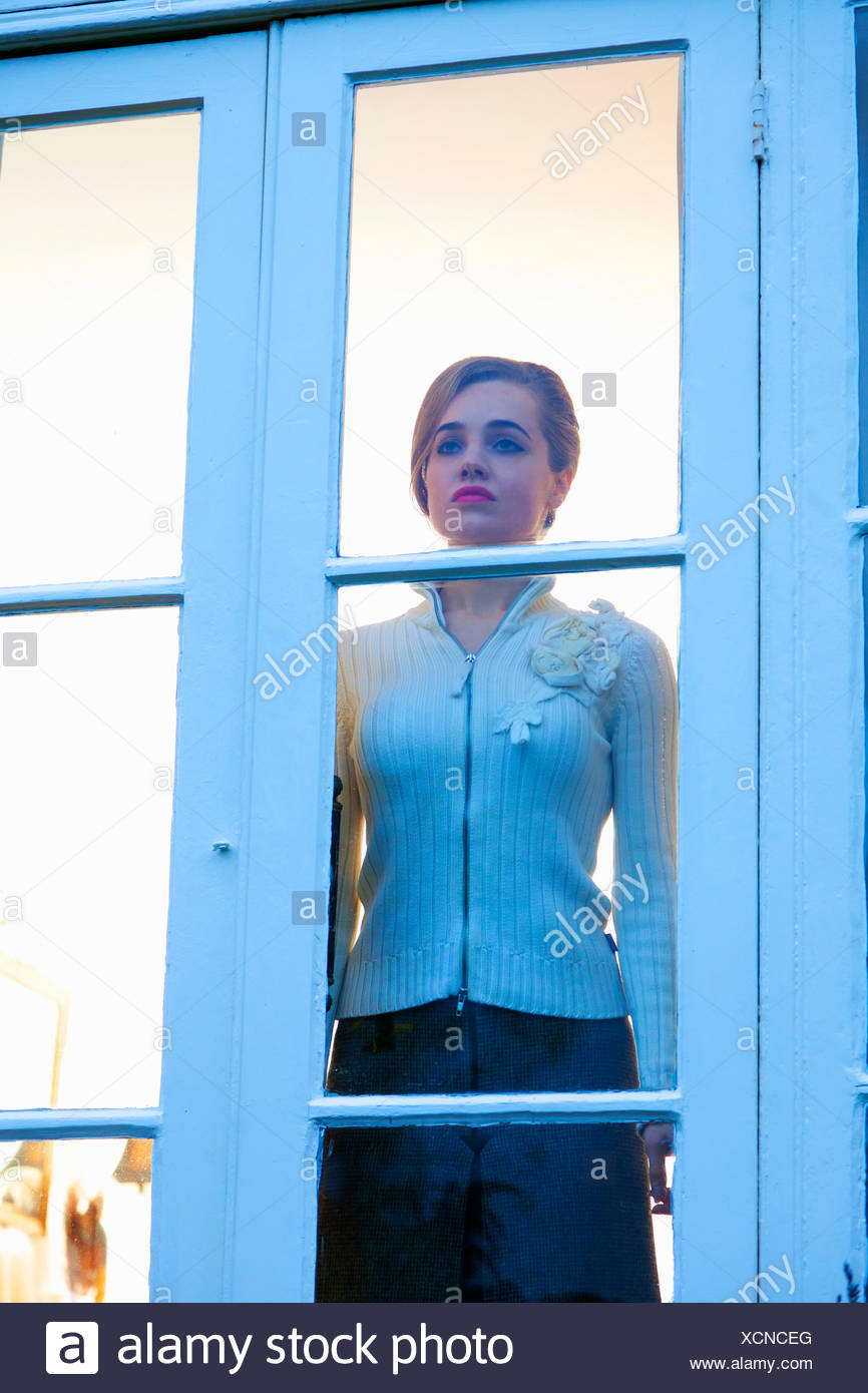 Woman looking out glass door - Stock Image