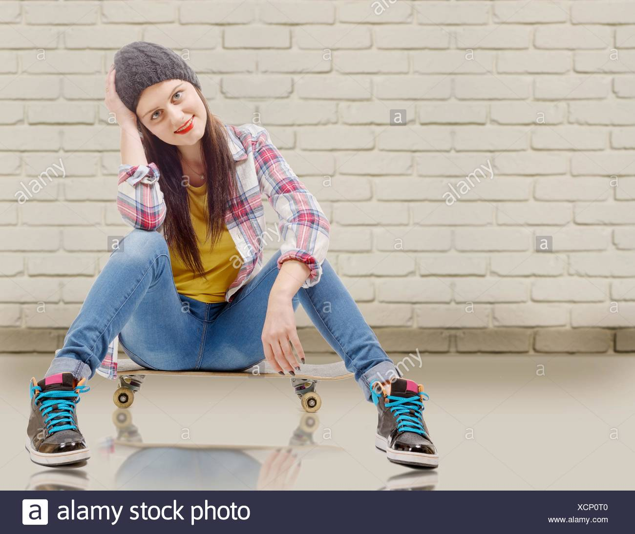 25abec96e0f Beautiful young woman posing with a skateboard