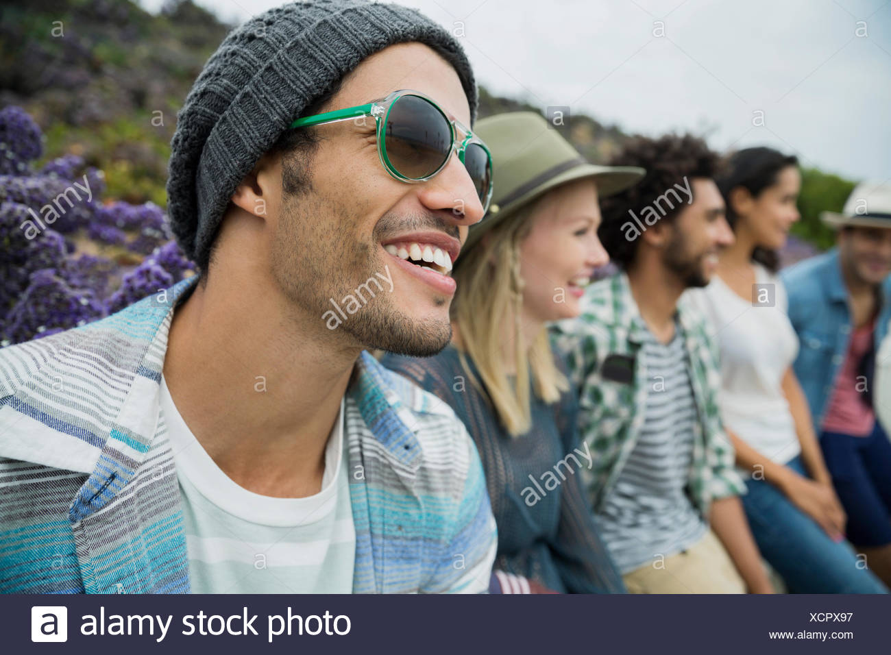 Smiling friends sitting in a row - Stock Image