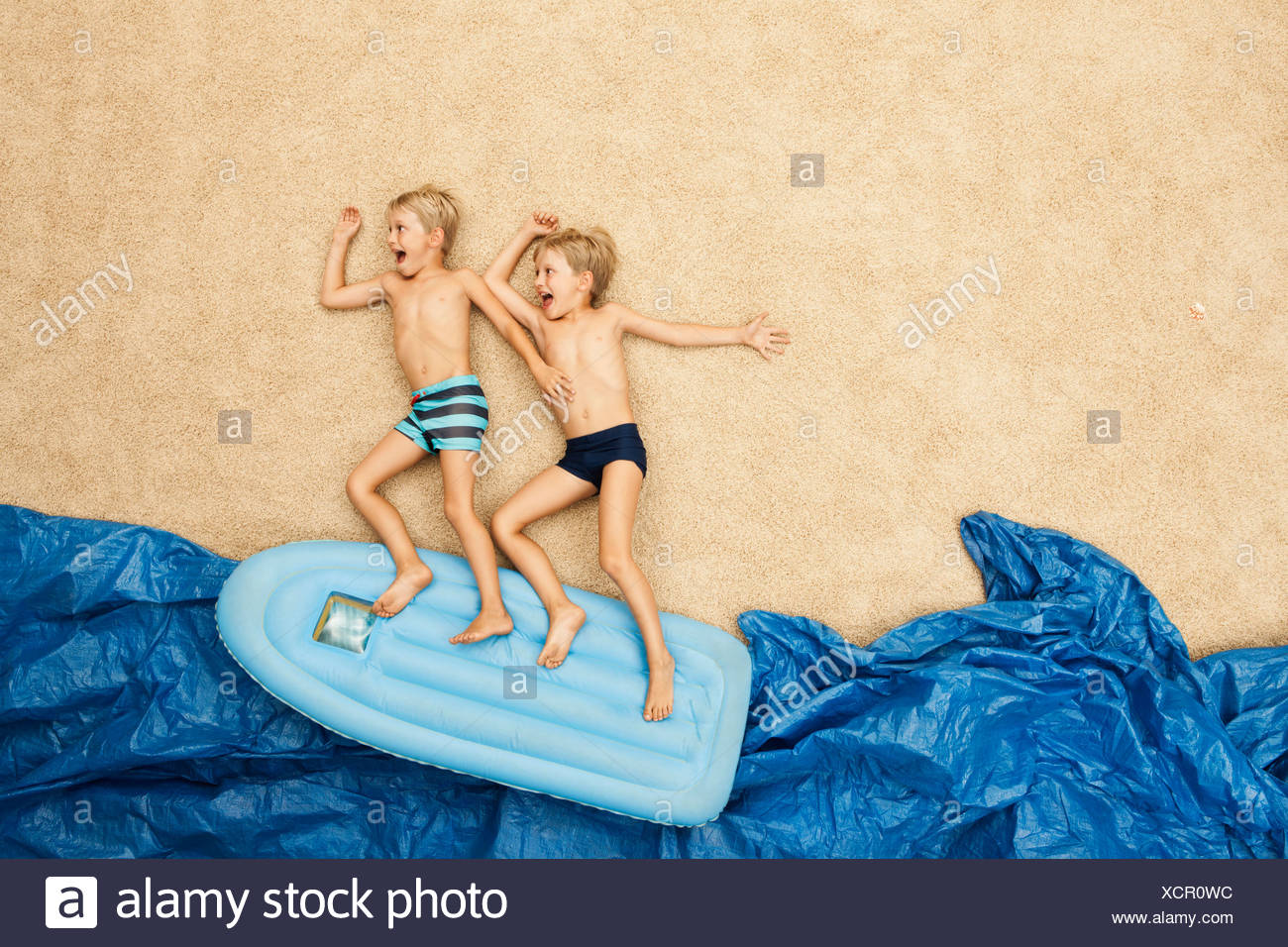 Germany, Boys on inflatable raft in water at beach - Stock Image