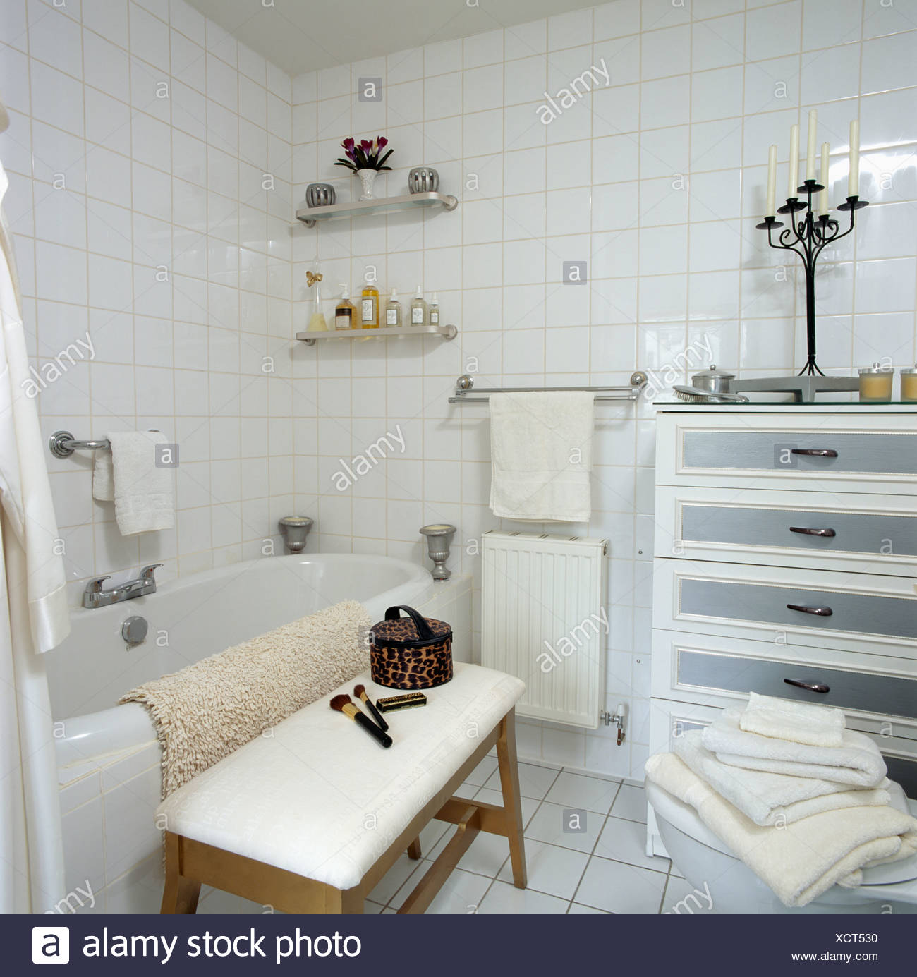 White tiled bathroom with small chest-of-drawers and upholstered ...