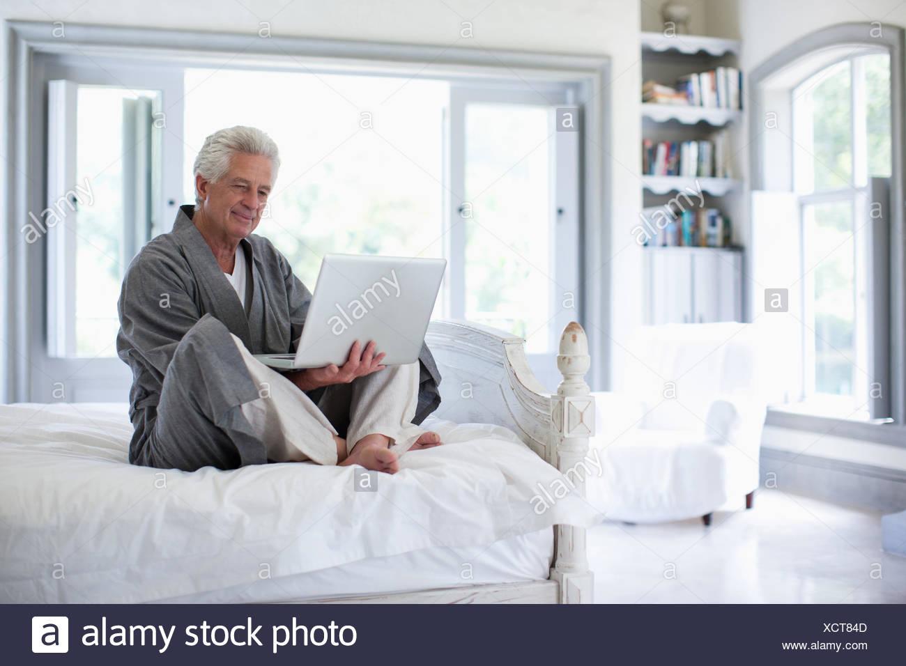 Senior man in bathrobe using laptop in bedroom - Stock Image