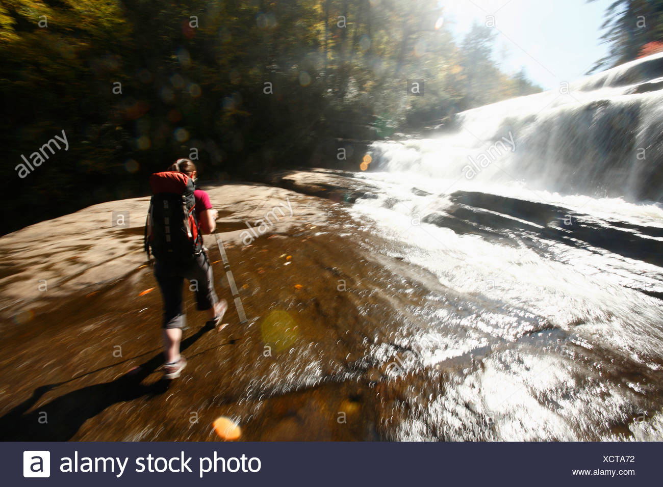 Motion blur of woman walking at base of waterfall. - Stock Image