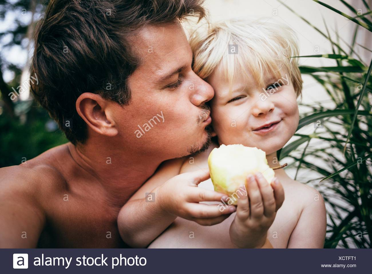 Head and shoulders of father kissing son on cheek, Bludenz, Vorarlberg, Austria - Stock Image