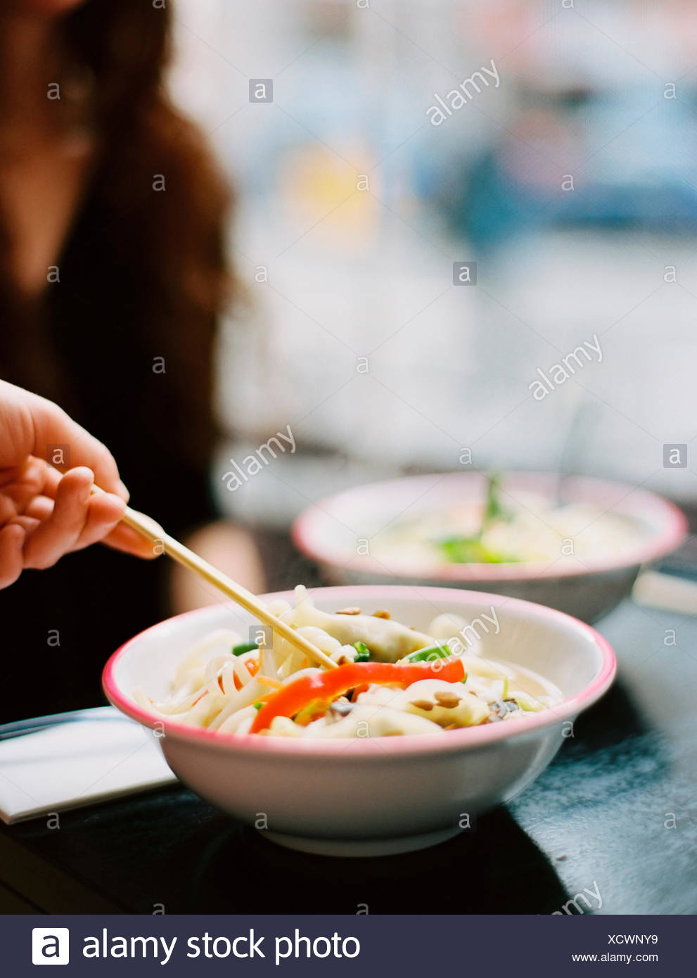 A person's hand holding chopsticks and stirring a dish of noodles. - Stock Image