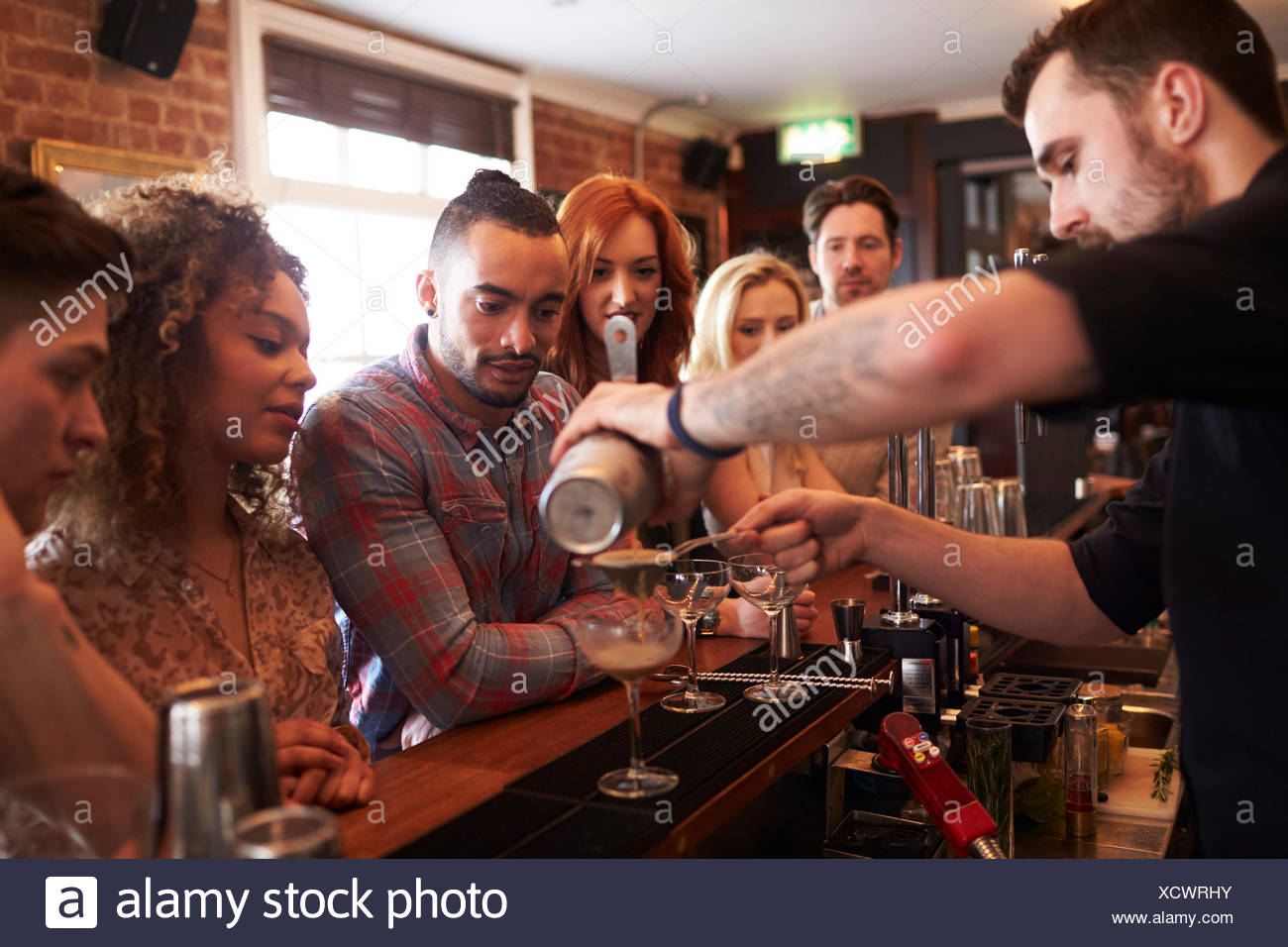 Bartender Giving Cocktail Making Lesson to Friends In Bar - Stock Image