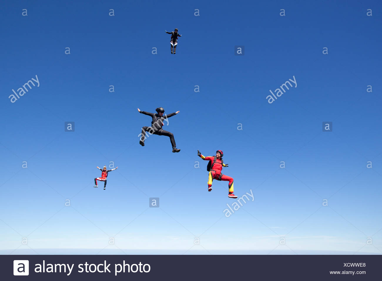 People skydiving over clouds - Stock Image