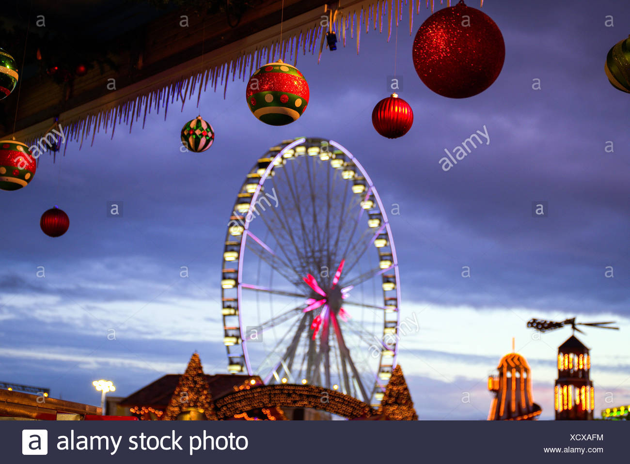 low angle view of christmas decorations hanging from roof against ferris wheel