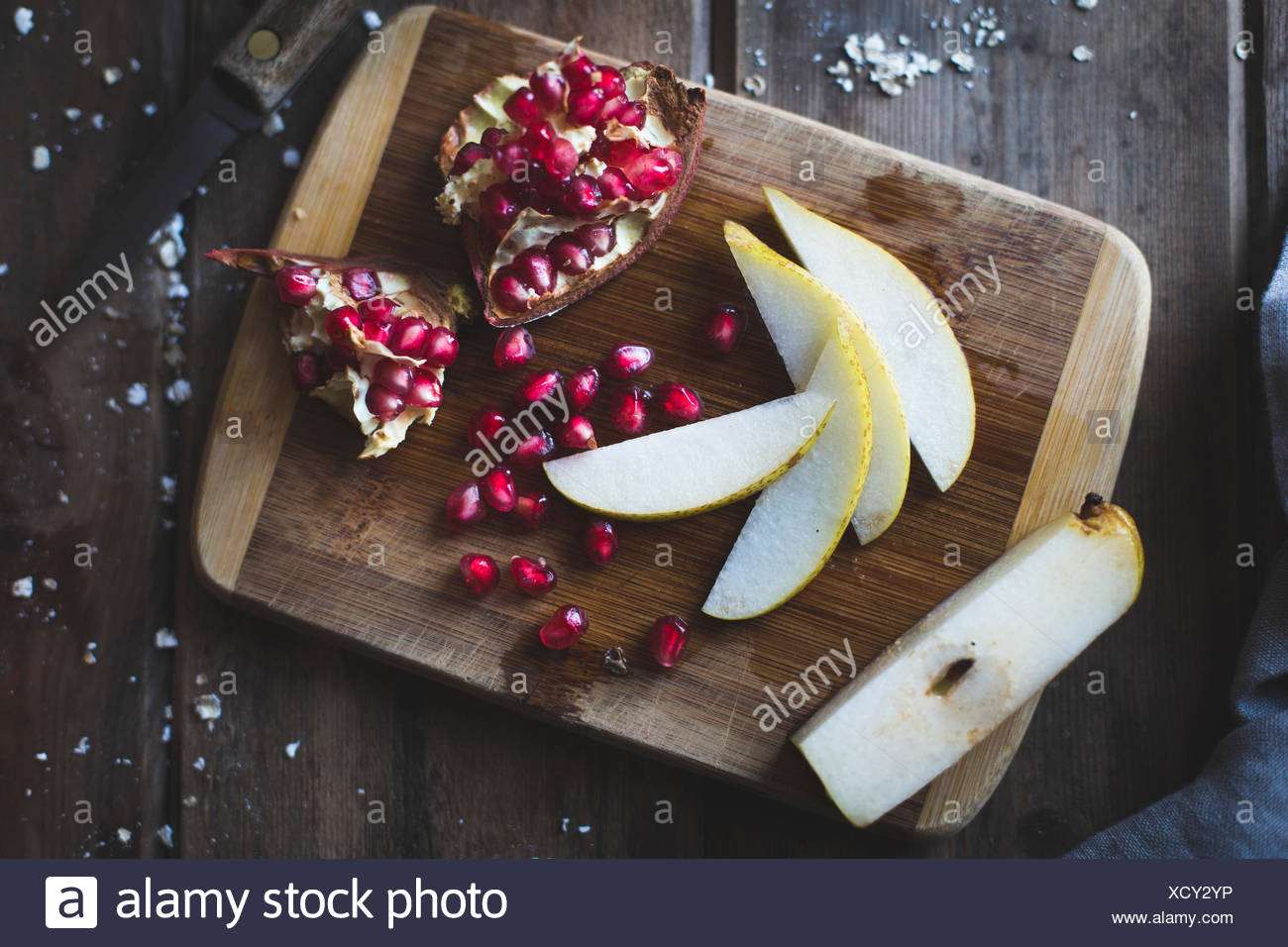 Pomegranate and Pear on a chopping board - Stock Image
