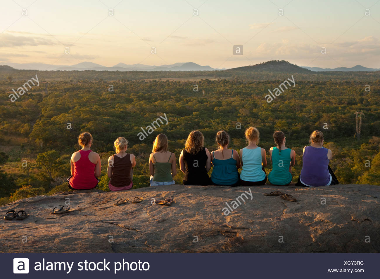 A Row Of Young Women Sitting On A Rock Ledge Viewing The African Landscape; Manica, Mozambique, Africa - Stock Image