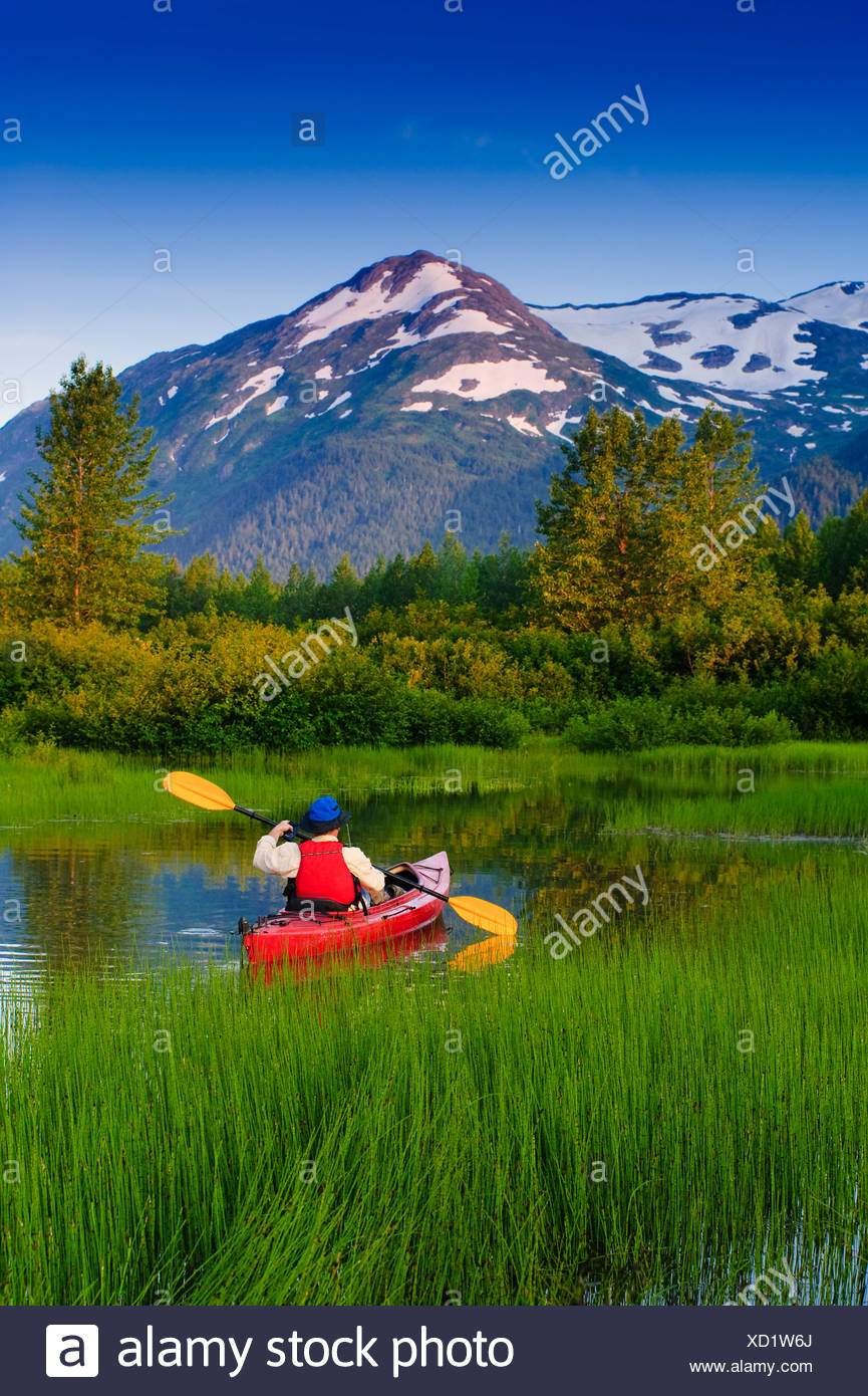 Man in a kayak paddling in a small lake in Portage Valley, Southcentral, Alaska, Summer - Stock Image