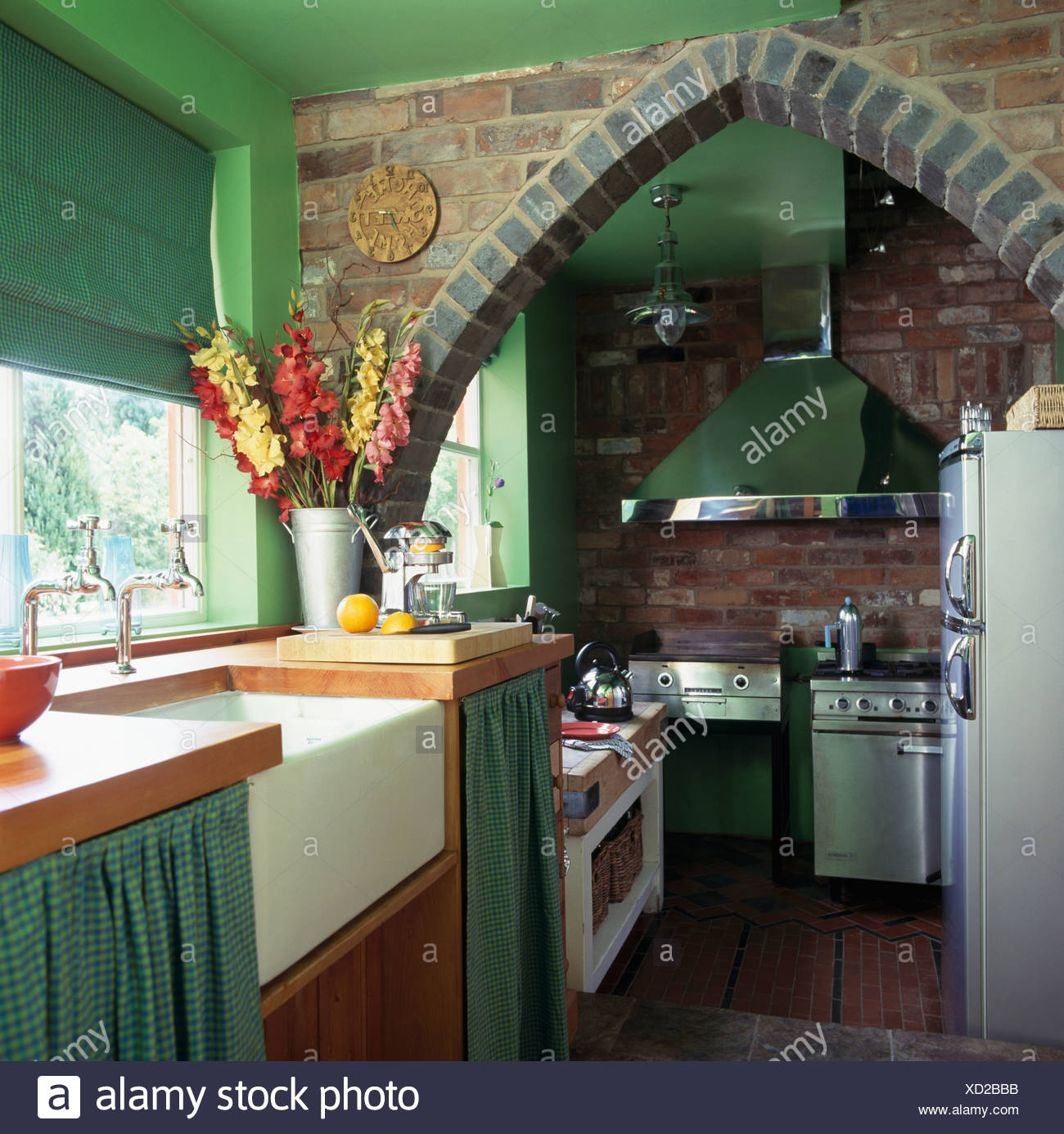 Brick Arch In Small Green Kitchen With Green Blind On Window Above Belfast  Sink In Fitted Unit With Green Checked Drapes