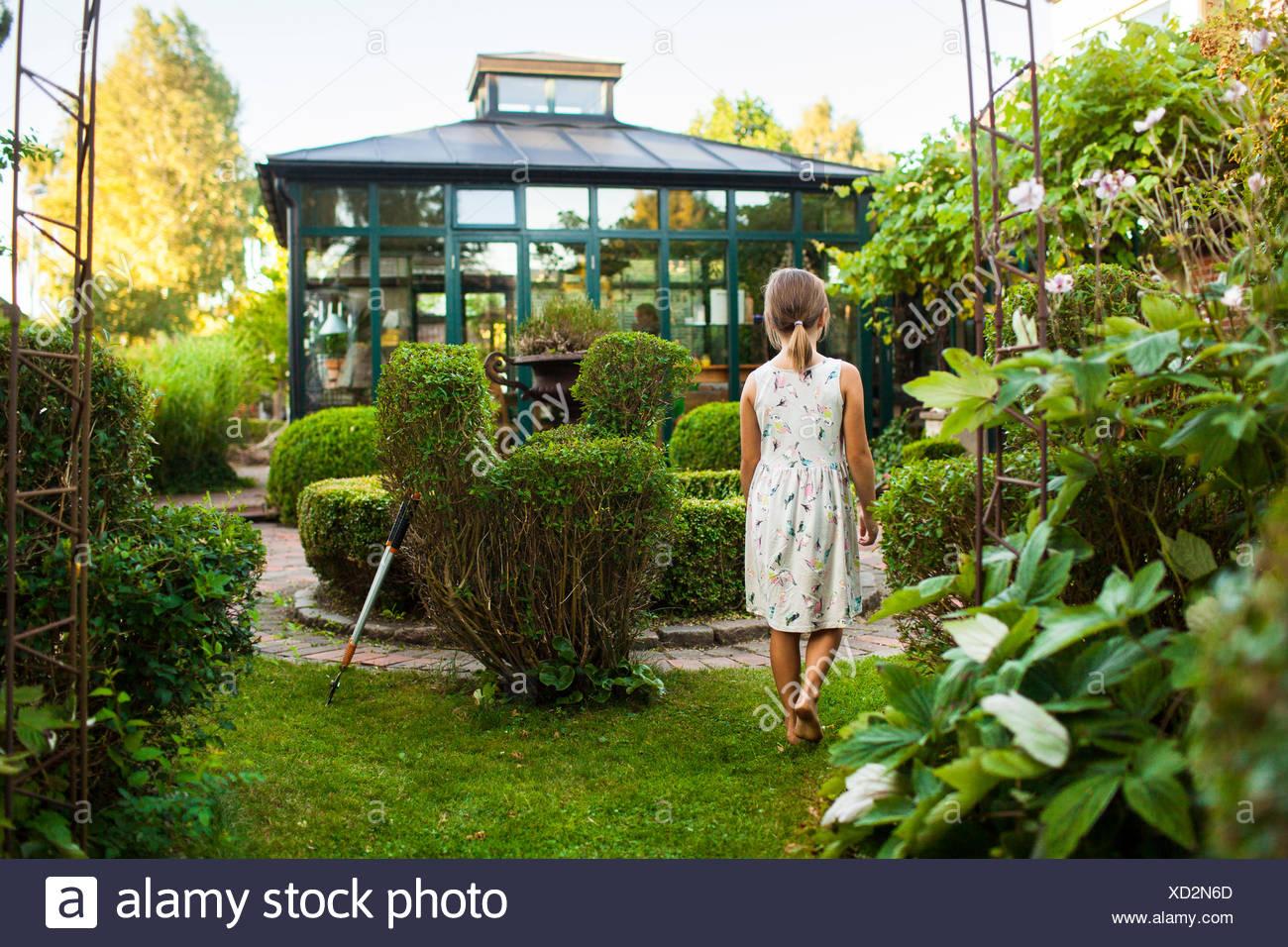 Rear view of girl walking in garden - Stock Image