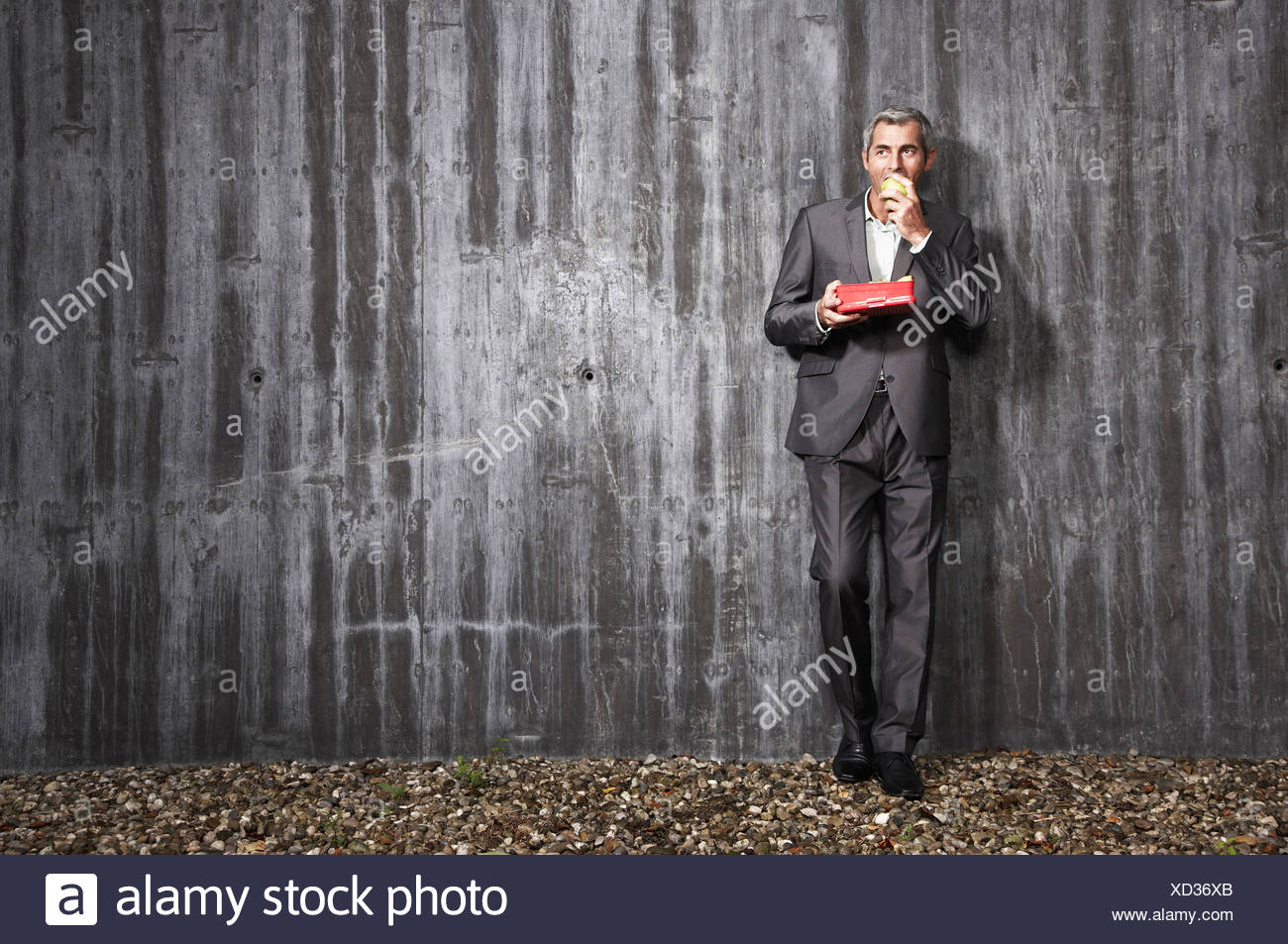 businessman holding box with fruits and eating apple - Stock Image