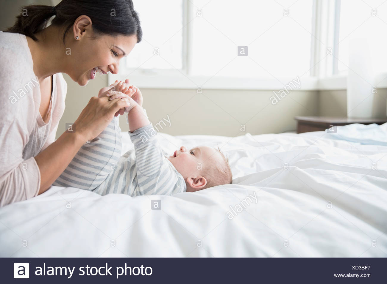 Mother playing with baby on bed - Stock Image