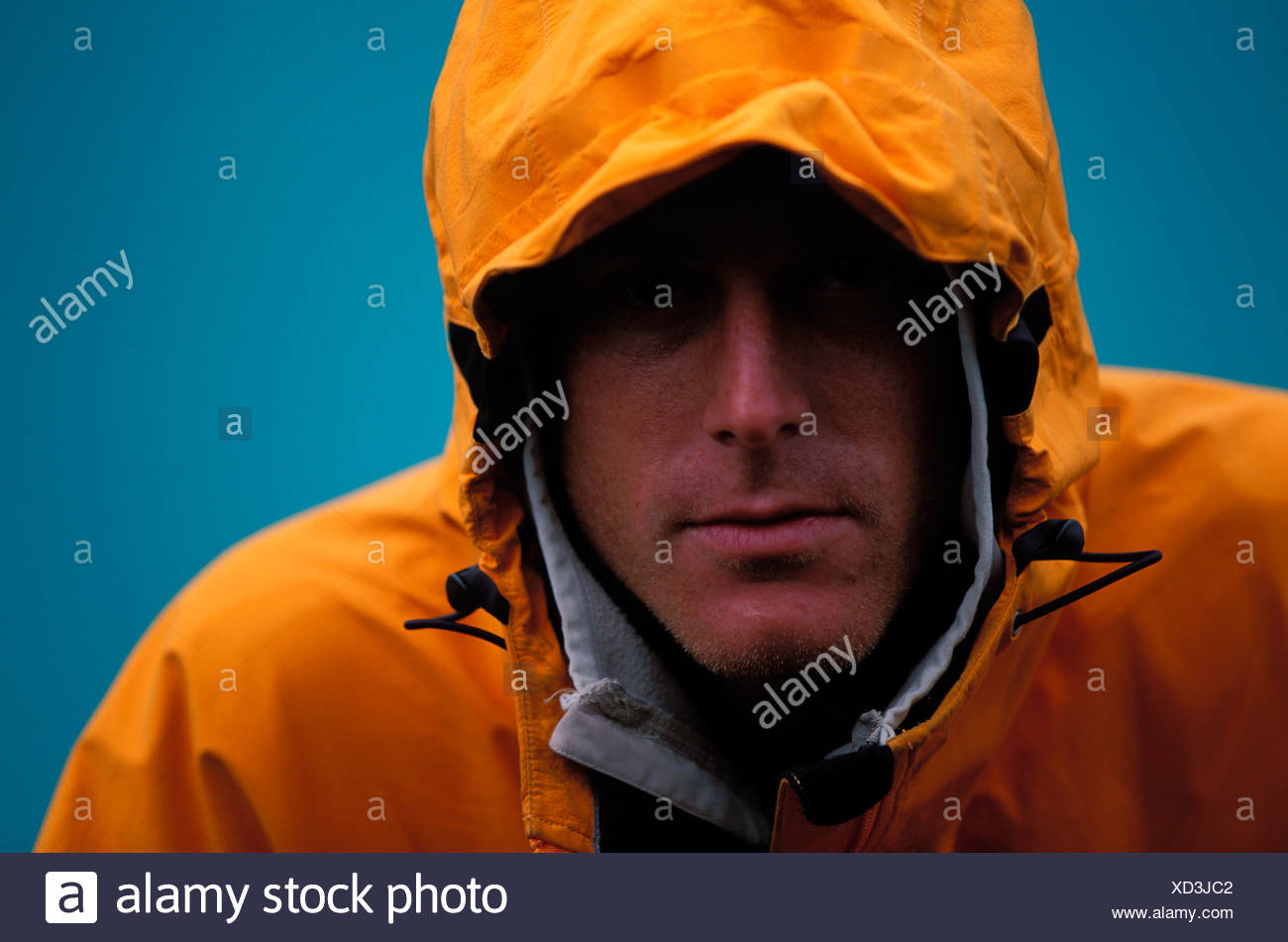 Headshot / portrait of a male climber with a yellow jacket and hood on. - Stock Image