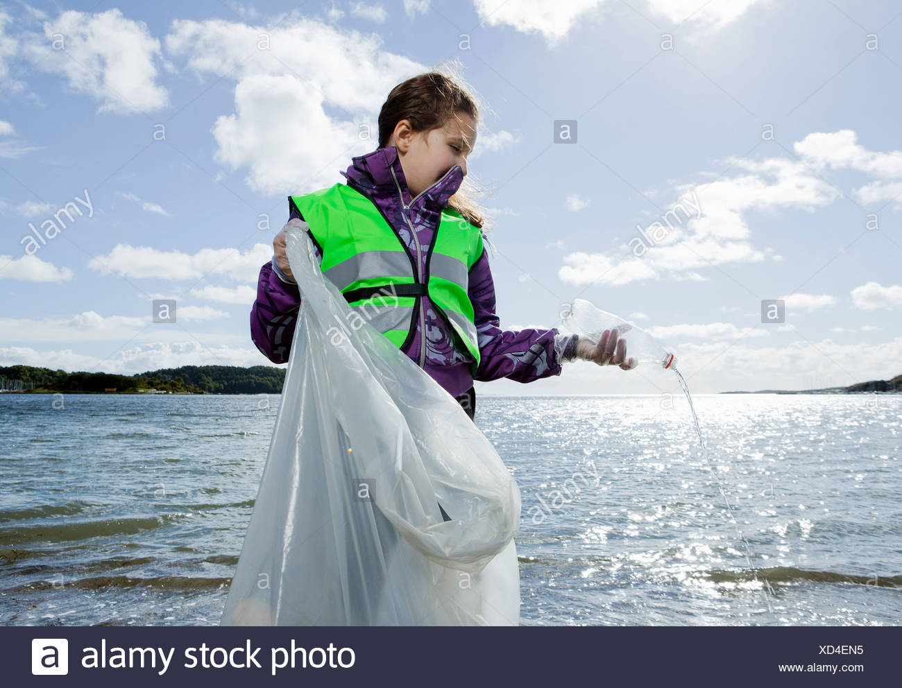 Girl in safety vest cleaning beach - Stock Image