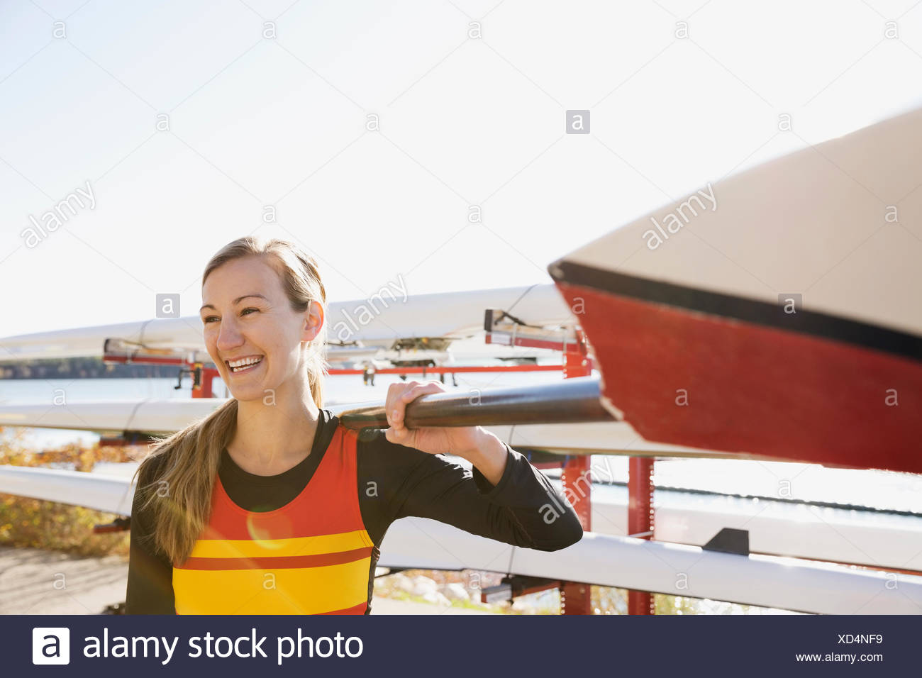 Smiling rower carrying oar - Stock Image