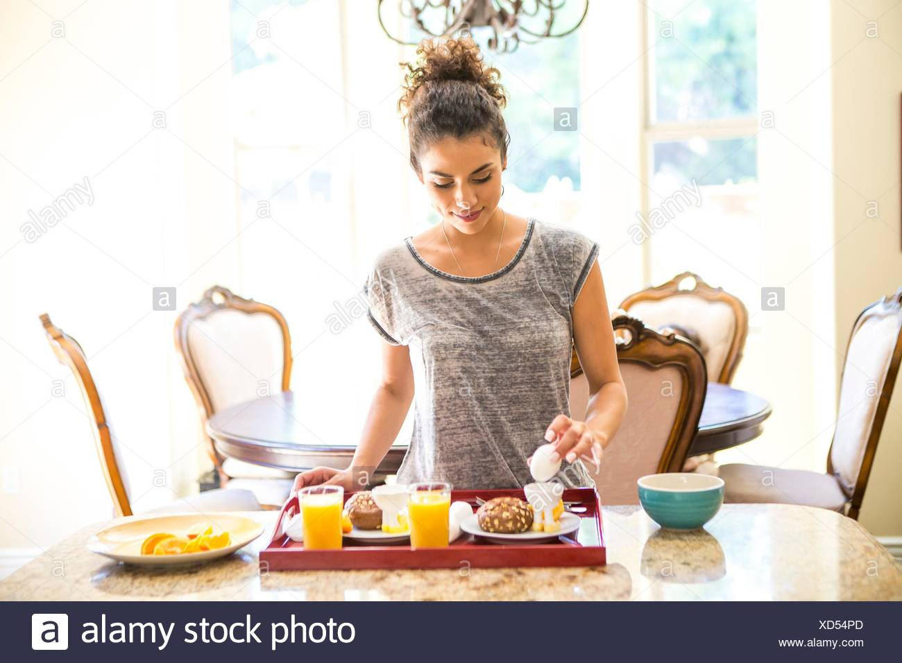 Young woman at home preparing breakfast tray, looking down holding egg - Stock Image