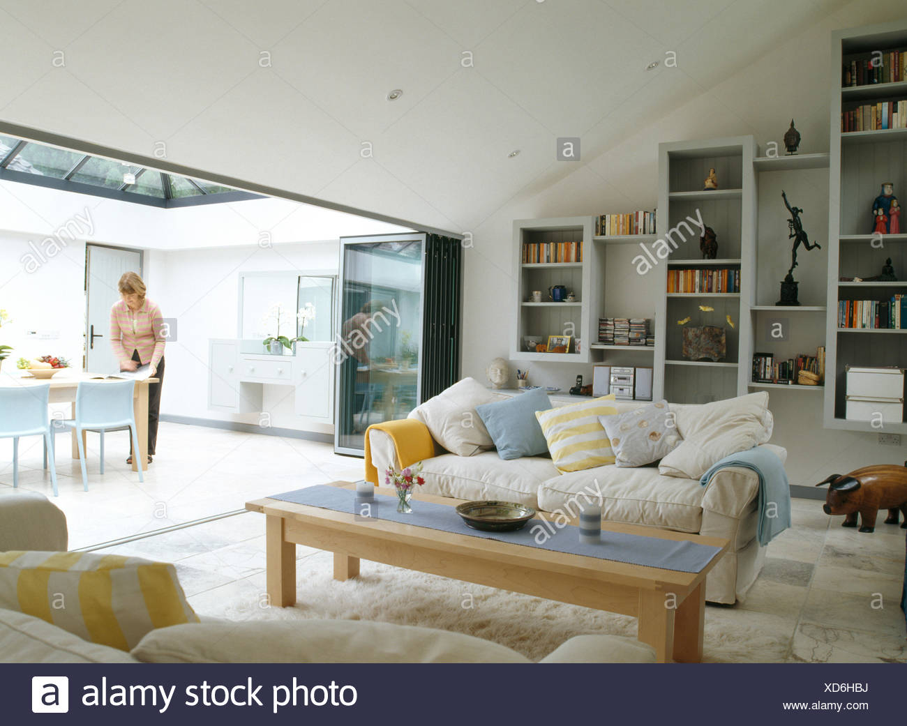 Modern living room with view of woman setting the table in dining ...