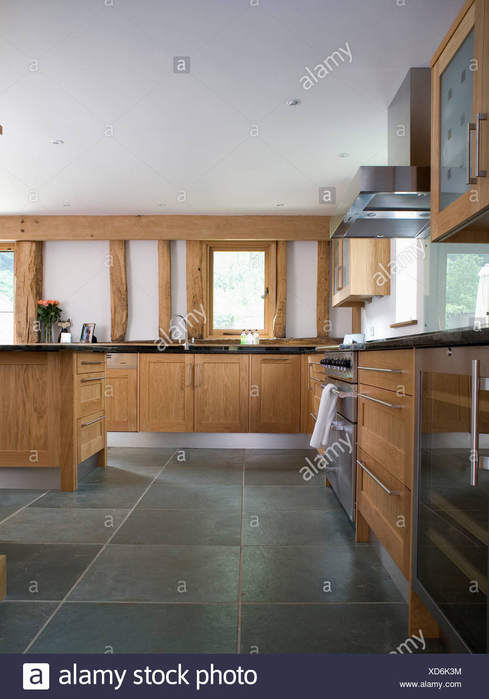 Slate flooring in large modern country kitchen with pale wood fitted units