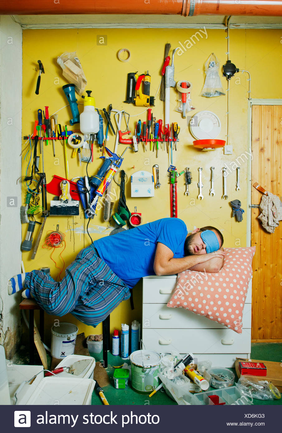 Man sleeping on workshop's table - Stock Image