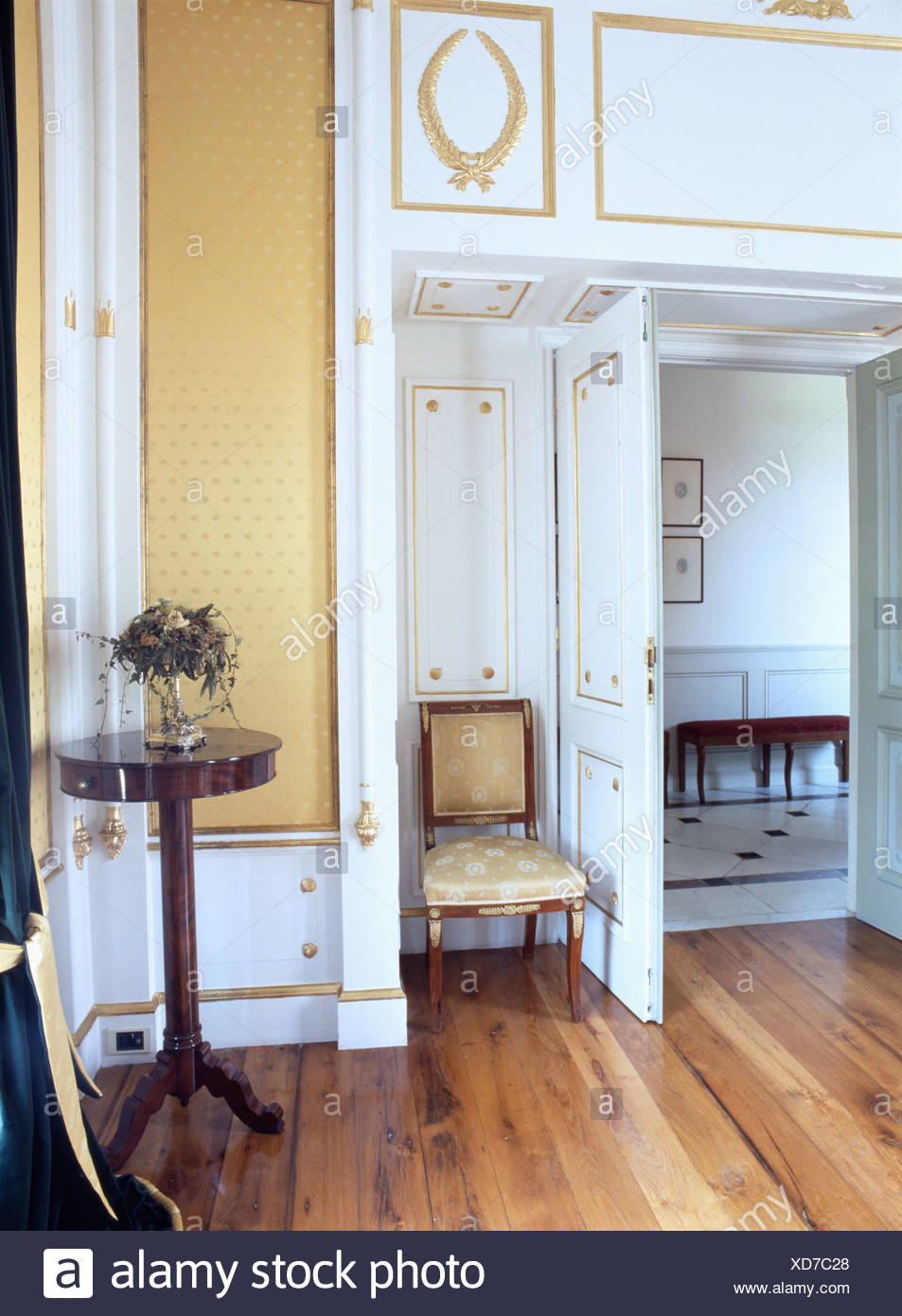 Antique Chair Beside Open Double Doors In Opulent Country Dining Room With Gilded Paintwork And Wooden Flooring