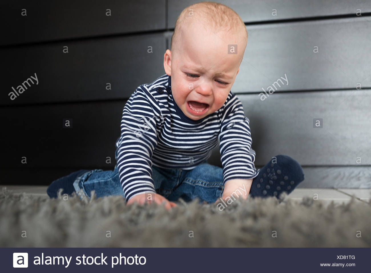 Crying baby boy sitting on rug in living room - Stock Image
