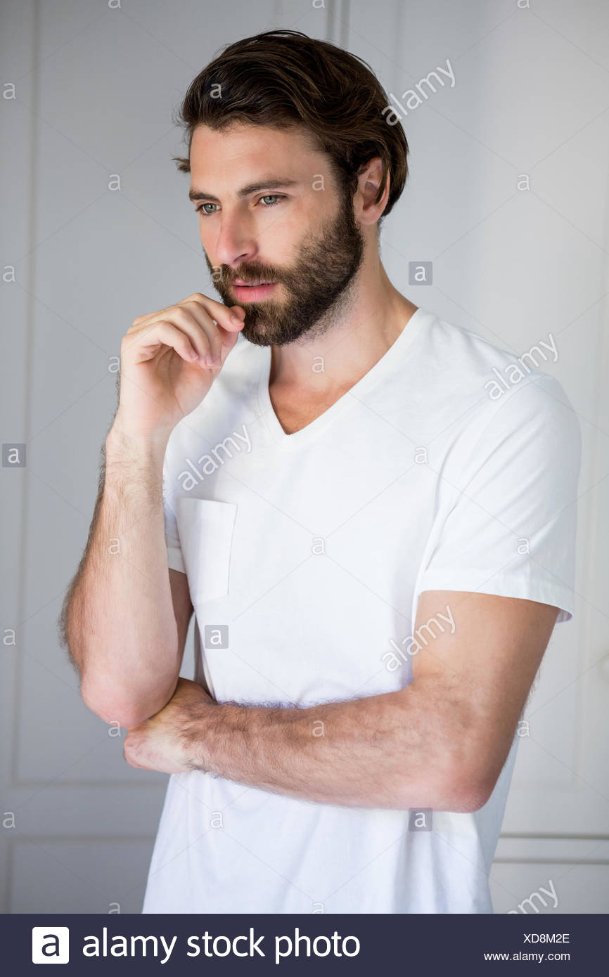 Tense man standing in bedroom - Stock Image