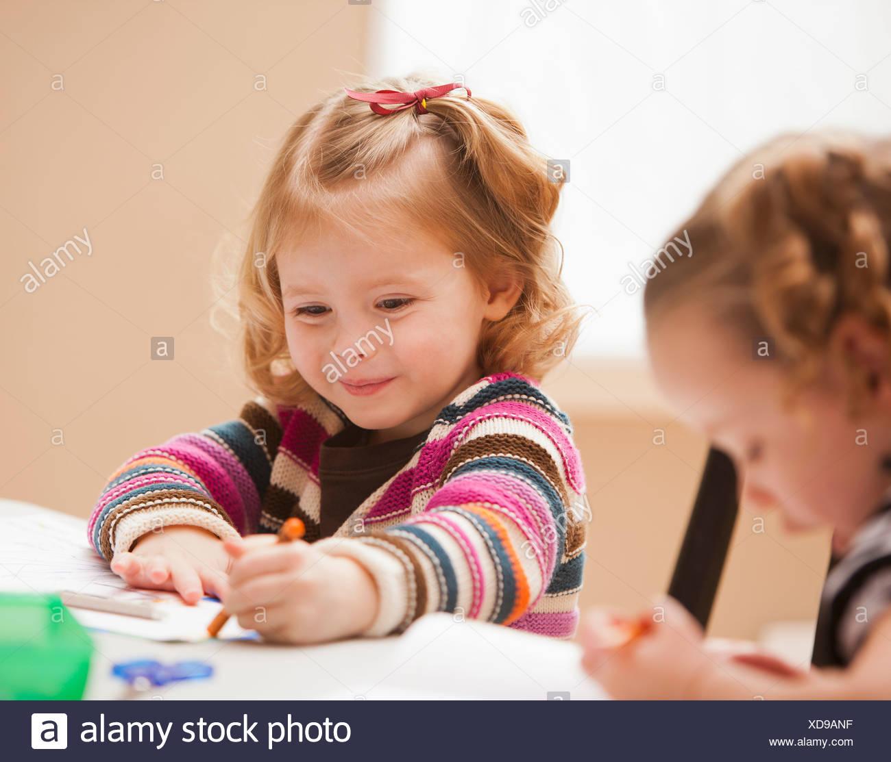 Girl (4-5) drawing in kindergarten - Stock Image