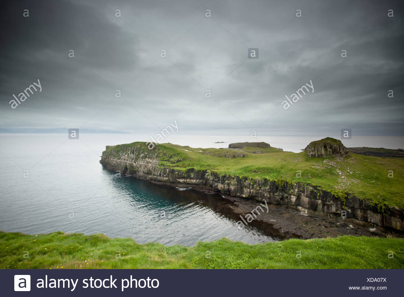 A Rock Ledge Along The Shoreline Under Dark Clouds; Papey Island Iceland - Stock Image