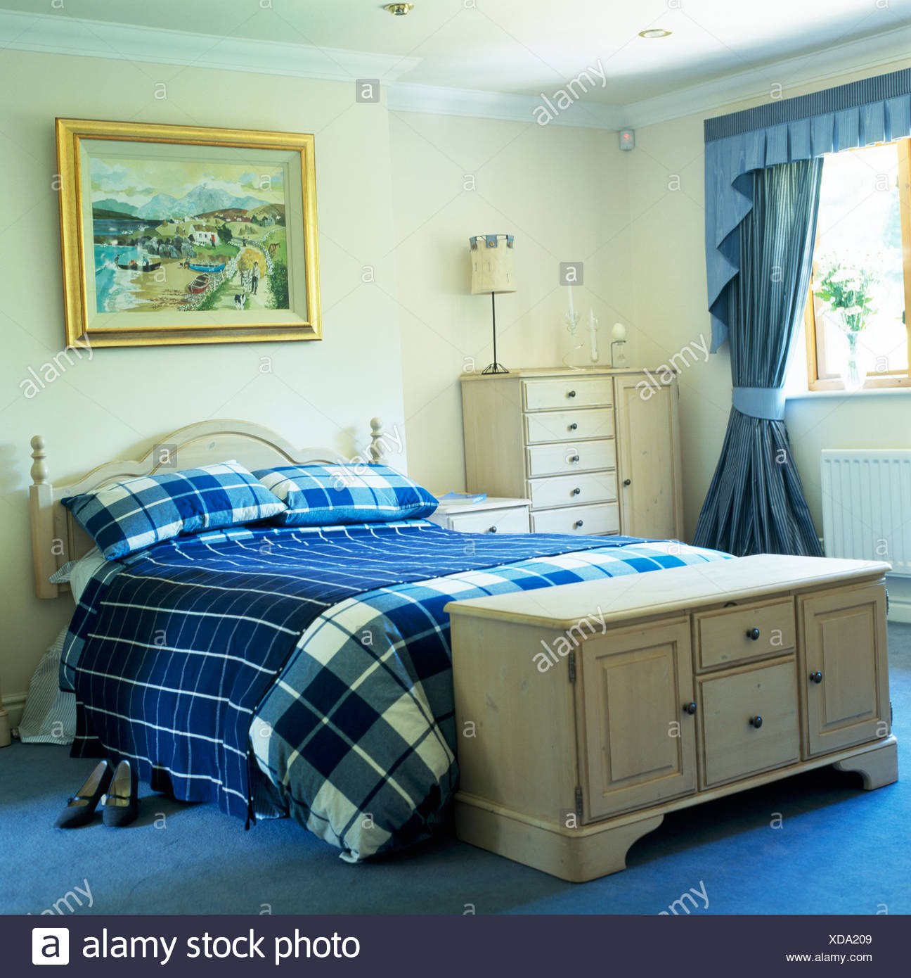Pale wood chest below bed with blue checked bed-cover and throw in ...