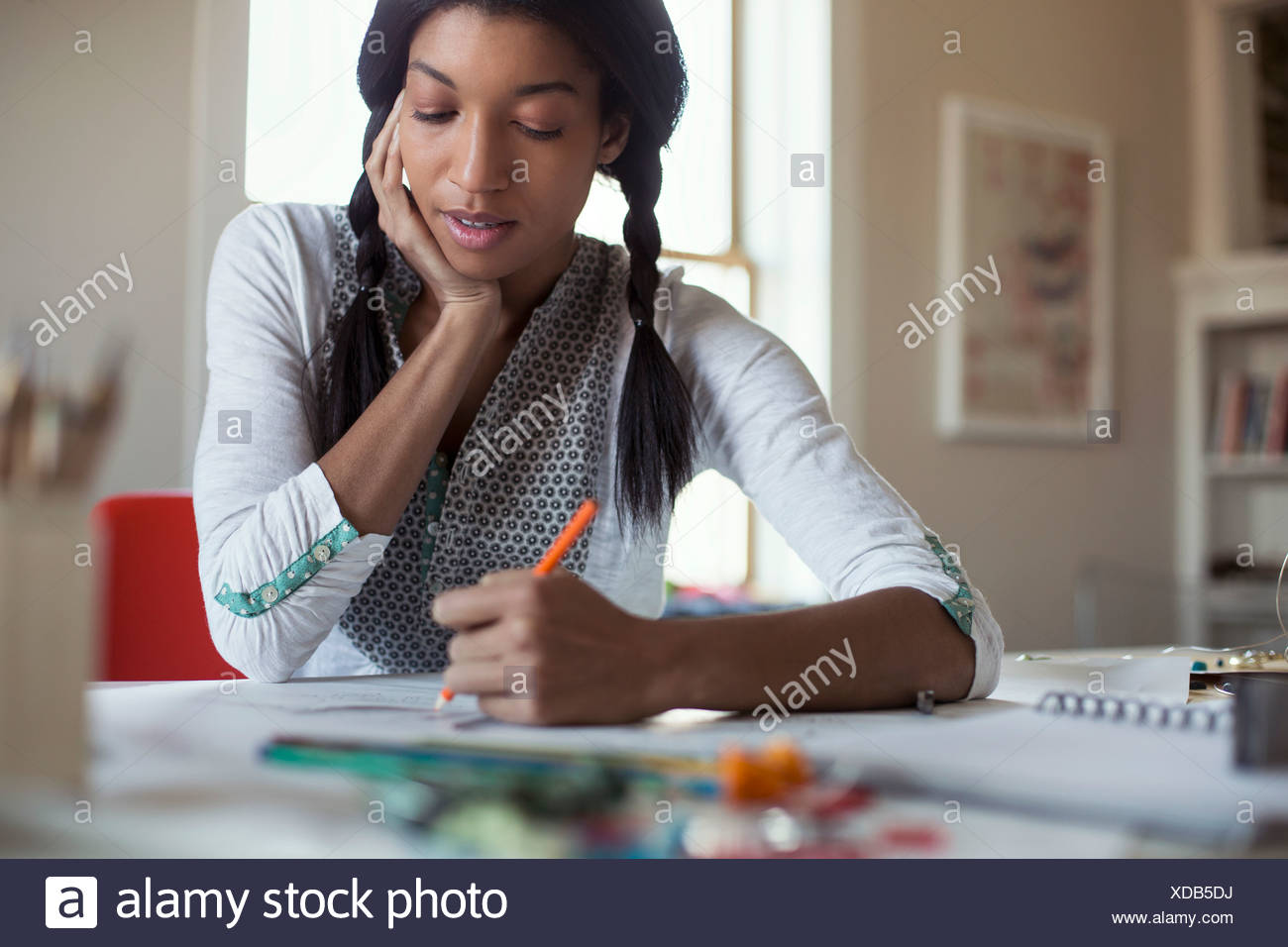 Mid adult female jewelry artist drawing at desk - Stock Image