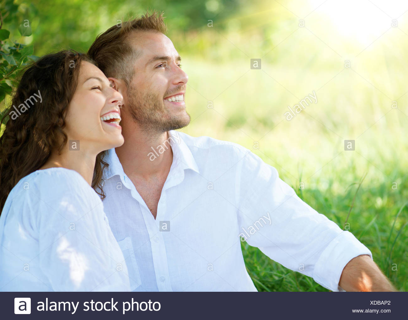 Happy Smiling Couple Relaxing in a Park - Stock Image